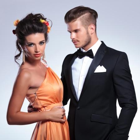 together with long tie: Primer plano de una pareja de moda joven con el hombre con la mujer mientras que ella mira a la c�mara. sobre fondo gris
