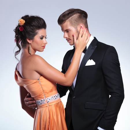 eachother: young fashion couple with woman caressing the mans face while looking at eachother. on gray background Stock Photo