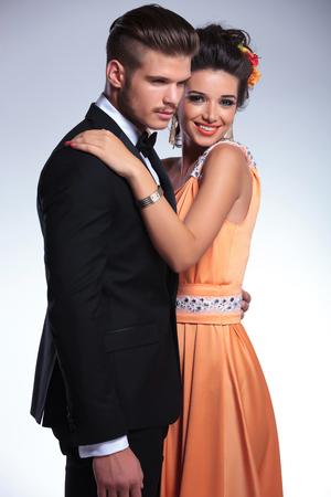 together with long tie: pareja de moda joven con la mujer con su mano sobre el hombro del hombre mientras sonr�e a la c�mara. sobre fondo gris