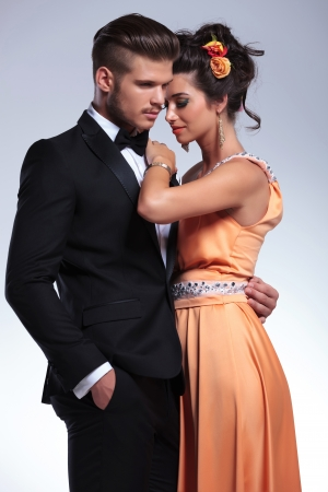 young fashion couple embracing romantically while the man holds his hand in his pocket and both looking away from the camera. on gray background photo