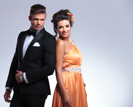 together with long tie: joven pareja de moda de pie espalda con espalda mientras ambos mirando a la c�mara. sobre fondo gris