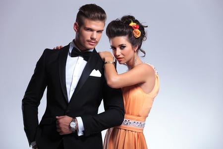 together with long tie: joven pareja de moda mirando a la c�mara con recelo. sobre fondo gris Foto de archivo