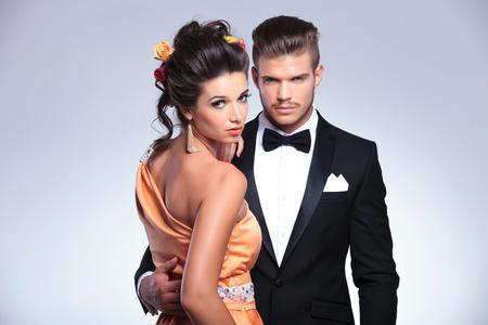 together with long tie: pareja joven de moda abrazar mientras que la mujer se ve en la c�mara sobre el hombro. sobre fondo gris