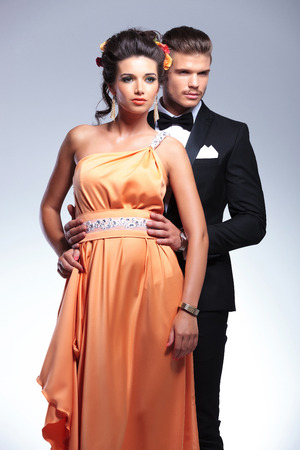 young fashion couple with man standing behind woman and holding her by the waist, both looking away from the camera. on gray background photo