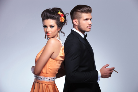 young fashion couple standing back to back while the man is holding a cigarette in his hand. on gray background photo