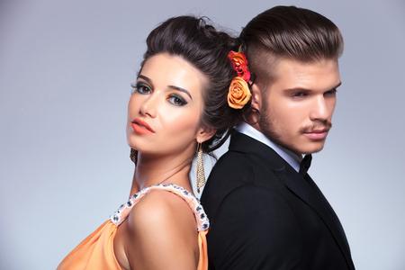together with long tie: joven pareja de moda de pie de espaldas y el hombre mirando a otro lado mientras que la mujer mirando a la c�mara. sobre fondo gris
