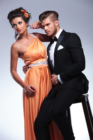 both: young fashion couple with man sitting on a chair and holding the woman while both looking away. on gray background