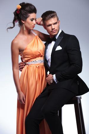 hombre sentado: pareja de moda joven con el hombre sentado la celebraci�n de mujer de pie mientras se mira lejos de la c�mara. sobre fondo gris Foto de archivo