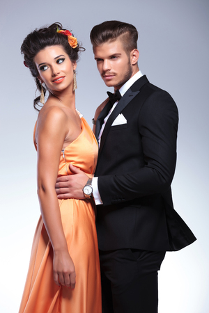 young fashion couple embracing while woman looking away, over her shoulder. on gray background photo