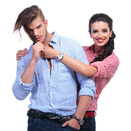 closeup of a young casual couple looking at the camera while she stands behind him and smiles. on white background photo