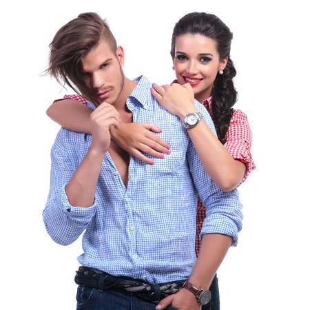 young casual couple with woman holding her hands over man's shoulder and smiling for the camera while he pulls his hair. on white background photo