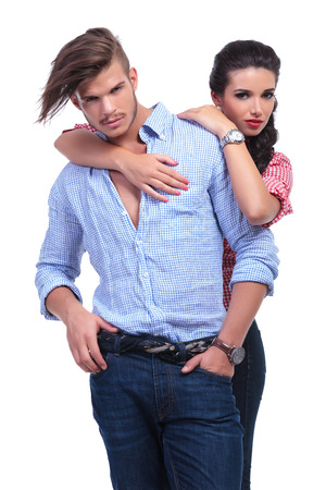 looking around: young casual couple with woman behind man, holding her hands around his neck while both looking into the camera. on white background