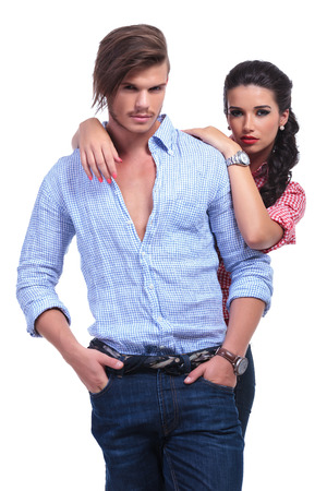 man behind: young casual couple with woman standing behind man with her hands on his shoulder while he is holding his hands in his pockets and looking into the camera. on white background