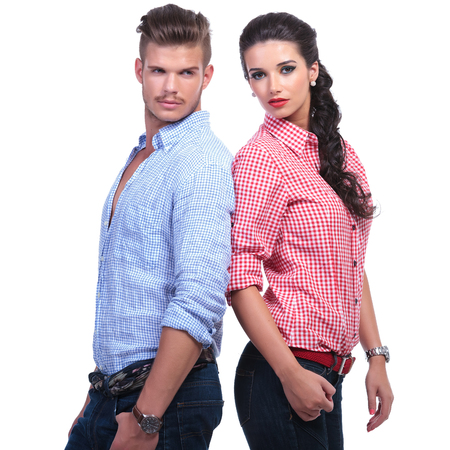 woman back: young casual couple standing back to back while the woman is looking into the camera and the man away. on white background Stock Photo