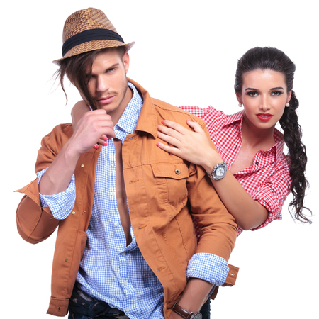 young casual couple looking into the camera while the man pulls down on his hair and the woman holds him by the shoulders from behind. on white background photo
