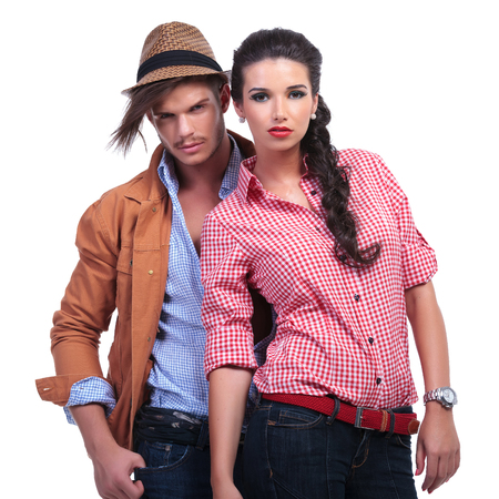 young casual couple with man behind woman, both looking into the camera. on white background Stock Photo - 22201038