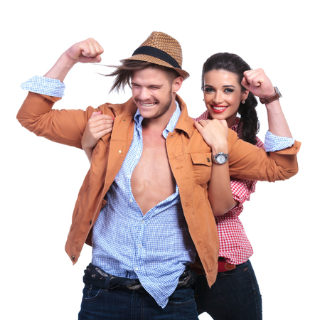 young casual couple smiling while man shows his biceps and woman holds him by his shoulders from behind and smiles for the camera. on white background photo