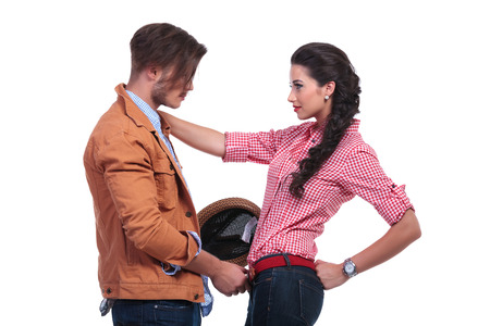 undoing: side view of a young casual couple looking at eachother while the man is undoing her belt while she is holding her hand on his shoulder. on white background