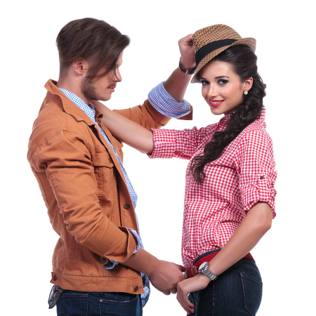 side view of a young casual couple playing while the woman looks into the camera and the man takes off her hat and belt. on white background photo