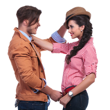 eachother: side view of a young casual couple looking at eachother and smiling while the man takes off her hat. on white background