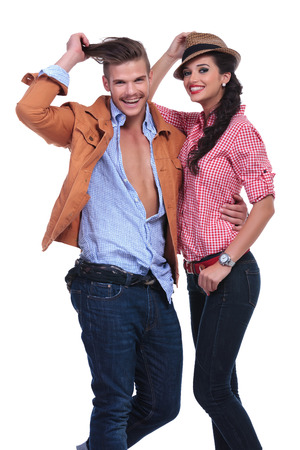 young casual couple laughing while the man pulls his hair and the woman holds her hat. on white background photo