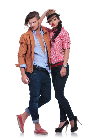 full length portrait of a young casual couple with the man holding the woman while looking away and she is holding her hat and looking into the camera. on white background photo