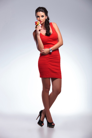 full length picture of a young beauty woman holding some roses and looking into the camera. on gray background photo