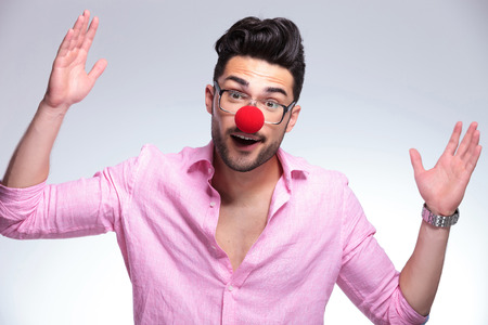 young fashion man with a red nose making gesures with his hands while looking into the camera. on a light background photo