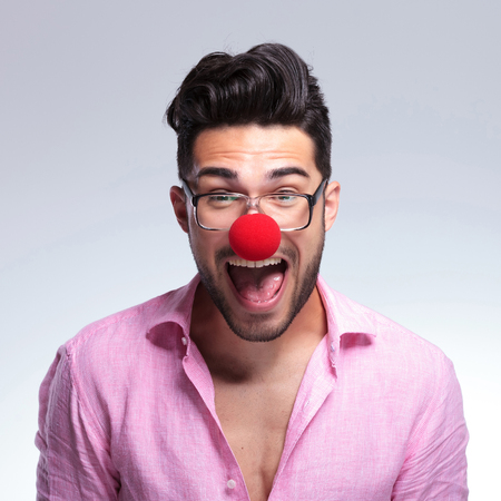 closeup portrait of a young fashion man with a clown red nose screaming at the camera. on a light background photo