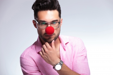 closeup of a young fashion man with a red nose looking pensively into the camera while touching his chin. on a light background photo