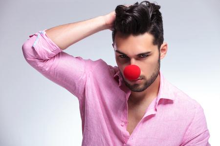 nariz roja: Primer plano de un hombre de moda joven con una nariz roja de payaso pasándose la mano por el pelo mientras mira a la cámara. sobre un fondo claro Foto de archivo