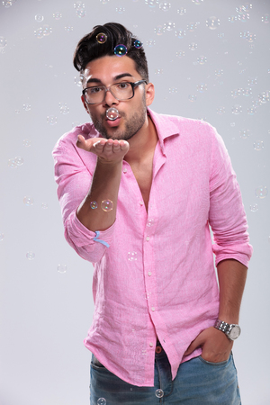 young fashion man blowing bubbles towards the camera while holding a hand in his pocket. on a white background photo