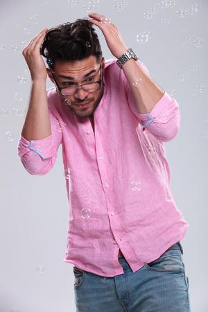 agachado: el hombre de moda joven agach�ndose por la ca�da de las burbujas. sobre un fondo blanco Foto de archivo