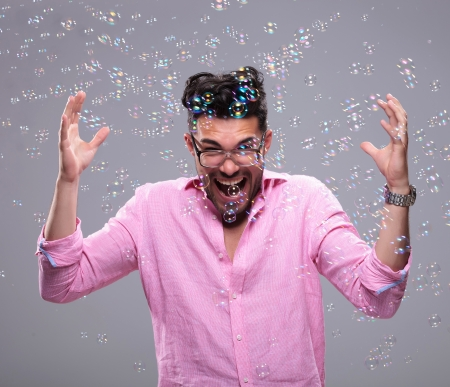 going crazy: young fashion man going crazy while bubbles fly around him. on a white background
