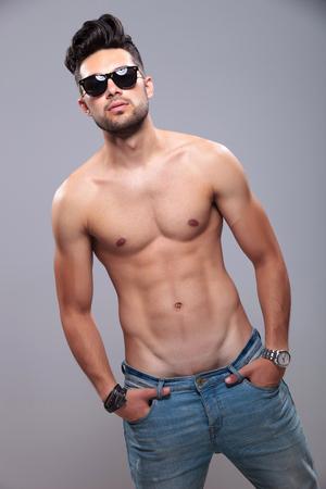 seins nus: torse nu jeune homme posant avec ses mains dans ses poches et en regardant la caméra. sur fond gris