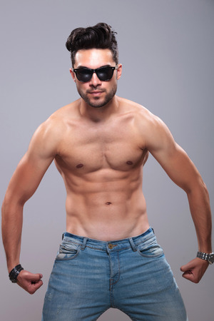 topless young man with lean body flexing his muscles while looking into the camera. on gray background photo