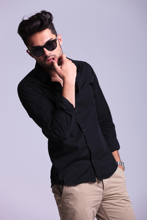sensually: young fashion man sensually touching his lower lip while holding his other hand in his pocket and looking into the camera. isolated on a gray background