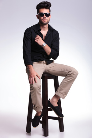 full length portrait of a young fashion man sitting on a chair and looking into the camera. on a light background photo
