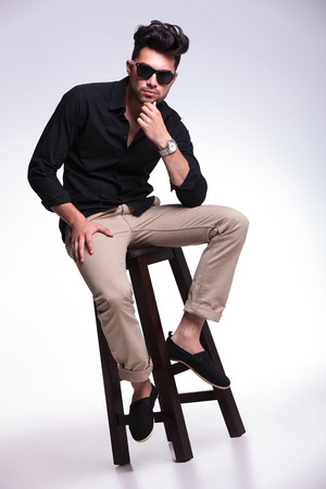 young fashion man sitting on a chair and holding his hand at his chin while looking pensively at the camera. on a light background  photo