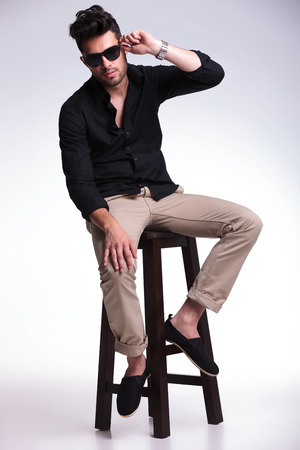full length portrait of a young fashion man sitting on a chair and adjusting his sunglasses while looking into the camera. on a light background photo