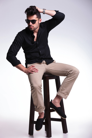 full length picture of a young fashion man sitting on a chair and fixing his hair while looking away from the camera. on a light background photo