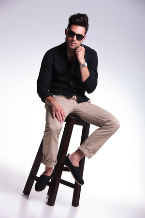 full length portrait of a young fashion man sitting on a chair and adjusting his shirt while looking at the camera. on a light background photo