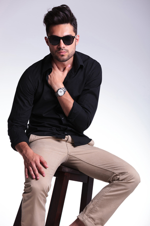 young fashion man sitting on a chair and holding his hand in his shirt while looking at the camera. on a light background photo