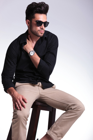 young fashion man sitting on a chair and looking away while holding his hand tucked in his shirt, at his shoulder. on a light background photo