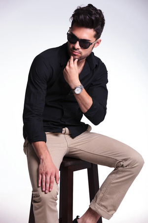 young fashion man sitting on a stool and thinking while looking away from the camera and touching his chin. on a light background photo