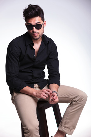 young fashion man sitting on a chair and adjusting his wrist watch while looking at the camera. on a light background photo