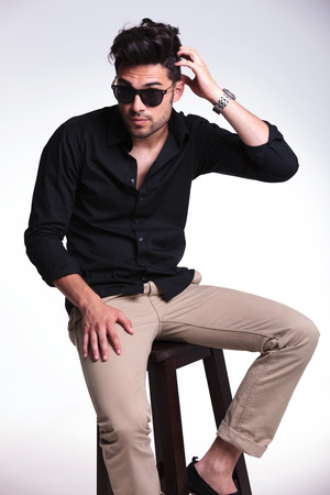 scratching head: young fashion man sitting on a chair and scratching his head while looking at the camera. on a light background