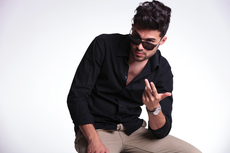 young fashion man sitting on a chair and looking at the camera over his lowered sunglasses. on a light background photo