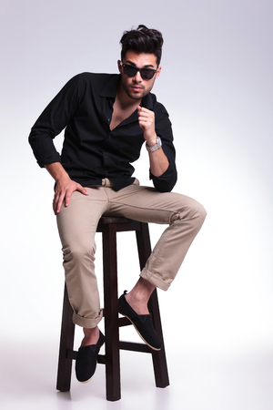 full length photo of a young fashion man sitting on a chair and looking into the camera with his eyebrows raised. on a light background photo
