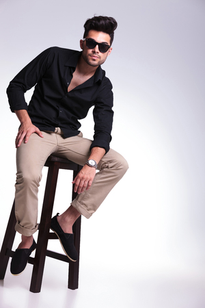 full length photo of a young fashion man sitting on a high stool and looking into the camera. on a light background photo